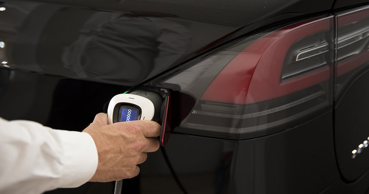 manly hand inserting charging cable into an electric car