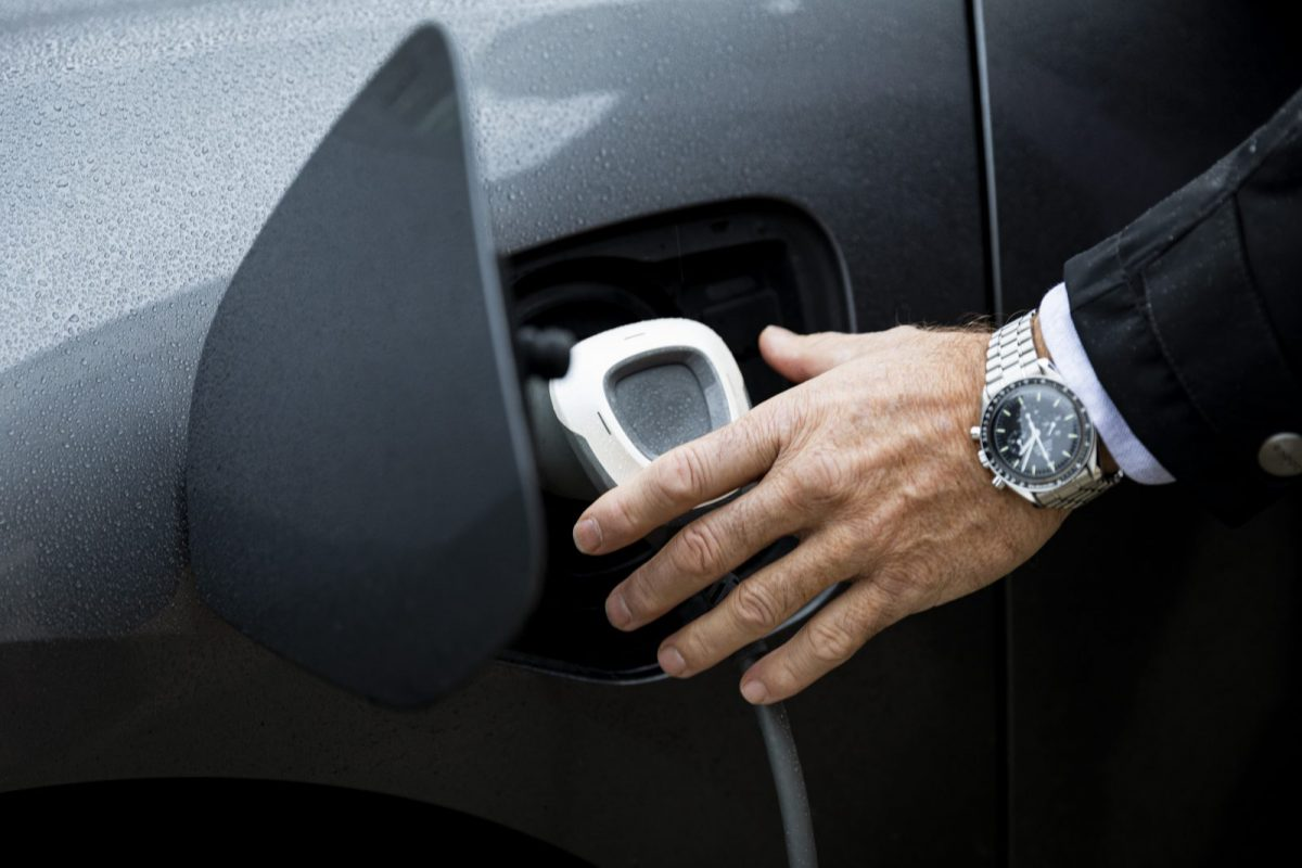 Man inserting charging cable in a electric car