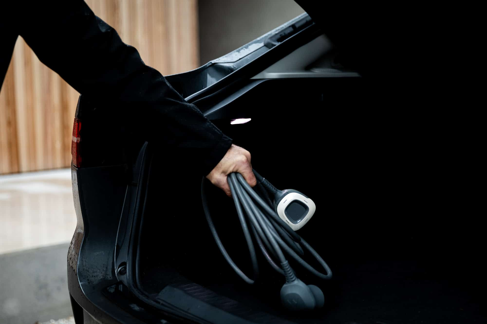 Man putting charging cables in his trunk