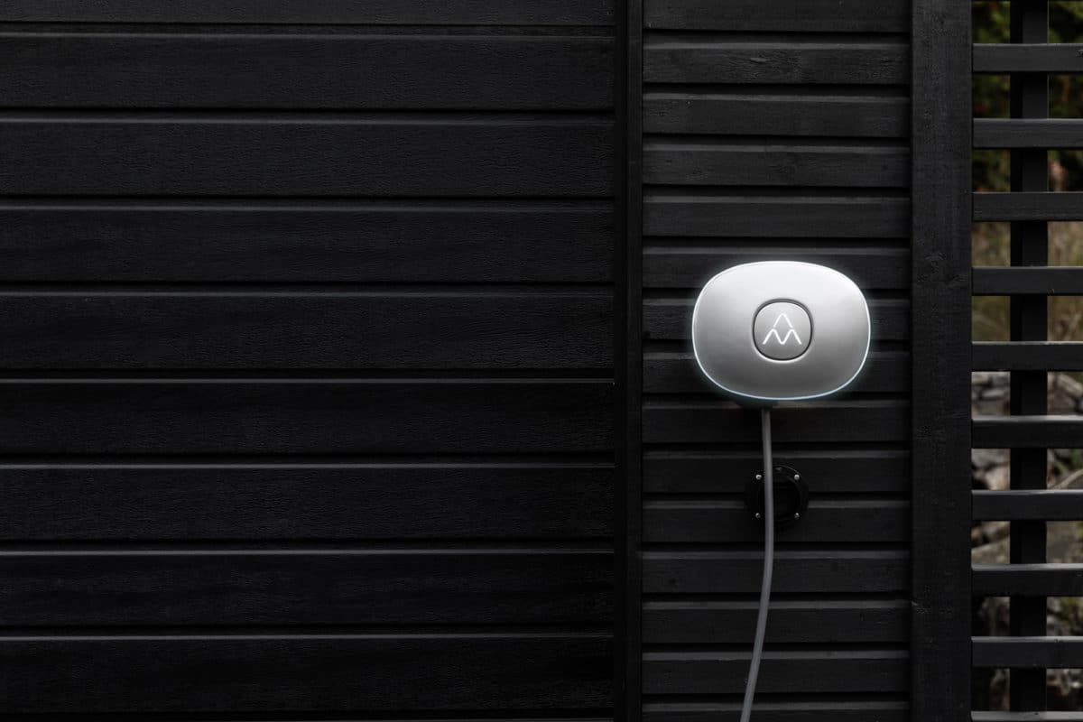 Charging station Charge Amps Halo on a black house facade