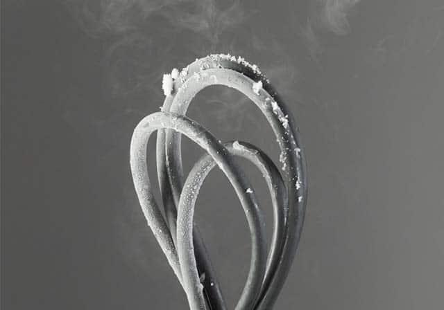 Charging cable bent in freezing temperature infront of grey background